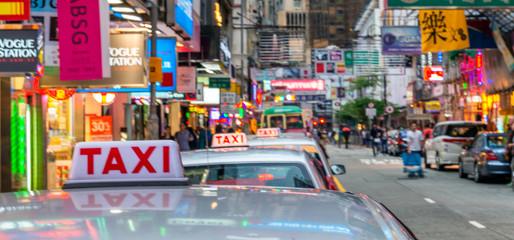 HONG KONG, CHINA - MAY 2014: City taxis and traffic at sunset. Hong Kong attracts 15 million visitors every year Wall mural