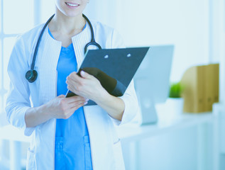 Young smiling female doctor with stethoscope holding a folder at a hospital's consulting room