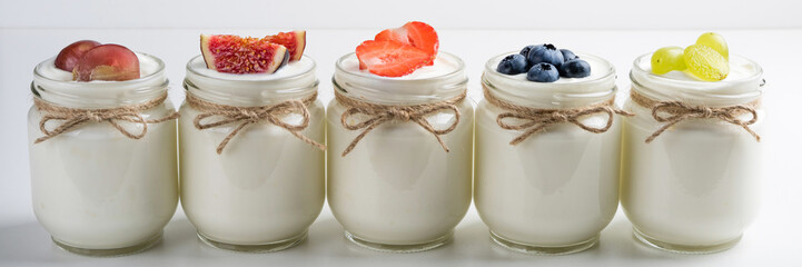Fresh yogurt. Breakfast with yogurt with fruits and berries. Healthy food concept. Long web format