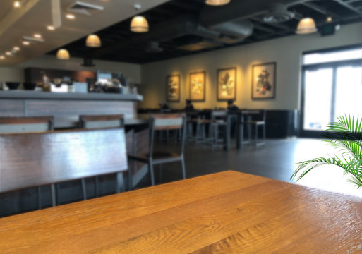 Blurred Coffee shop or pub background and perspective view of wooden table corner