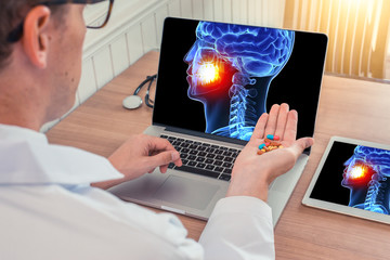 Doctor or dentist holding pills with x-ray of 3D skull head with pain in the teeth on a laptop. Digital tablet on the wooden desk