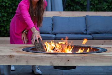 woman throws logs on fire pit in the garden on a summer day