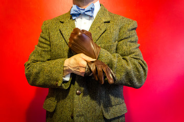 Portrait of Dapper Man in Tweed Suit Pulling on a Leather Glove. Strong Manly Determination in the Harsh Face of Cold Hands. Vintage Fashion and Style.