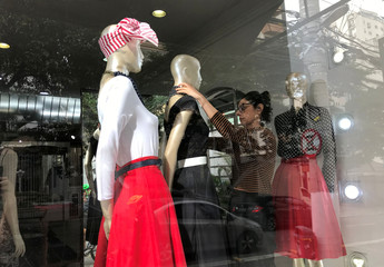 A shop assistant arranges clothes on a mannequin in Sao Paulo
