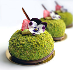 Close up of green textured pistachio desserts with edible pansy flowers and dried strawberries