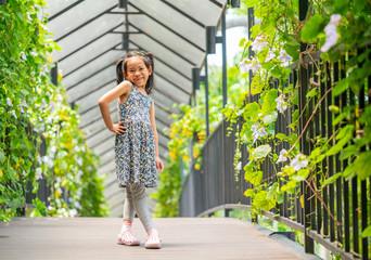 Little girl posing on the bridge garden
