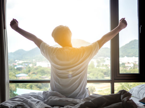 Man stretch his hands after waking up in bed at morning with sunlight