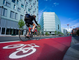 Cyclist in a symbol-marked, red bicycle lane in an urban area. Oslo, Norway.