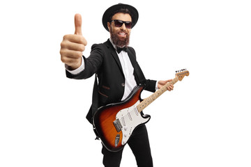 Cheerful male guitarist with an electric guitar showing thumbs up