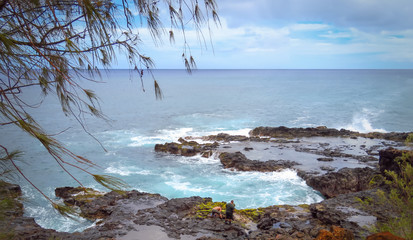 Panoramic landscape of two men looking for crabs at the rocky shore near Spouting Horn blowhole, Pacific Ocean, Kauai, Hawaii, USA