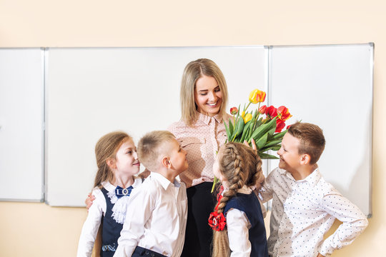 Beautiful children-students together in class at school give flowers to their best woman teacher