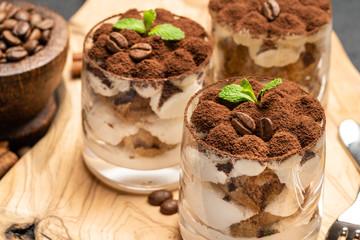 Classic tiramisu dessert in a glass on dark concrete background
