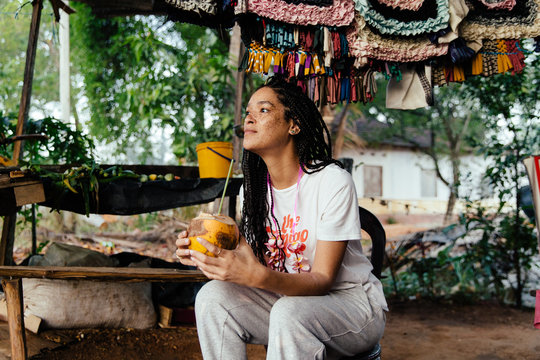 Woman Traveling Drinking Out Of A Coconut in And Exotic Location