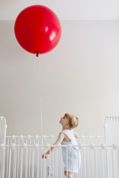 toddler in a crib holding a big red birthday balloon