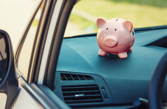 Pink piggy money box inside a car transportation. Saving money for vehicle purchase. Economic investment for future. Buy or loan automobile.