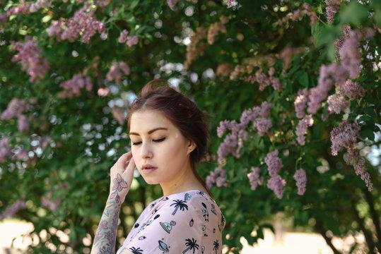 Young woman among lilac blossom