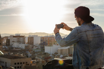 Young man takes a picture with the city in the background
