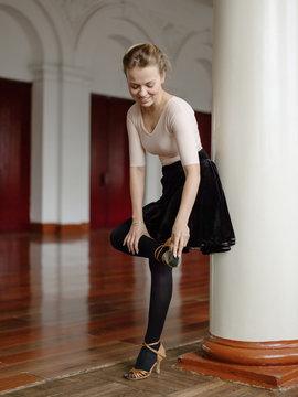 Cheerful girl brushing ballroom shoes in hall
