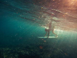 Surfer duckdiving wave on shallow reef