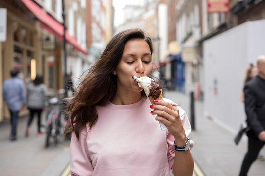Beautiful  young woman eating ice cream in Covent Garden, London