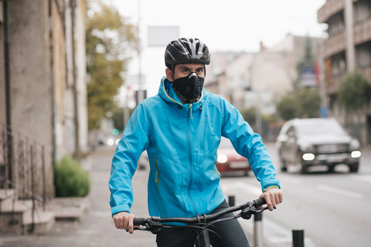 Young guy with face mask riding bike in the street