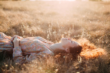Lovely curly woman enjoying summer sunset laying on the grass