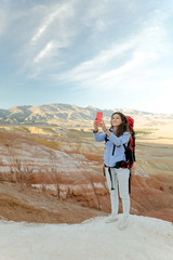 young girl traveler climbed the colored mountains and takes pictures on her phone