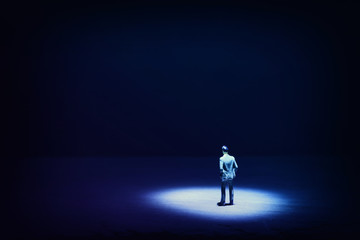 A picture of a miniature man stands in the spotlight looking forward.Concept of facing the unknown, taking a decision and finding solution.