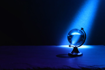 Small crystal globe in front of dark and dramatic light.global issues concept