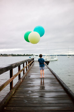 Boy on a jetty with three large helium filled balloons on string