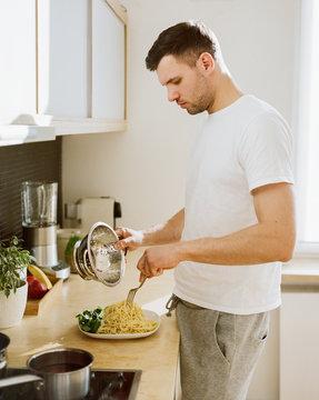 Man putting pasta onto plate