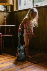 Young Girl Standing with Guitar