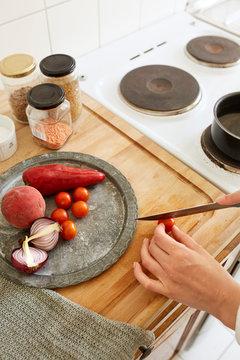 Woman cutting a tomato.