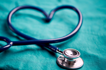 A stethoscope shaping a heart on a medical uniform, closeup