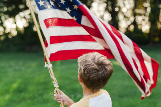 anonymous boy holding an American flag