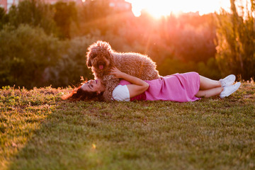 young owner woman with her brown spanish water dog having fun outdoors in a park at sunset. love...