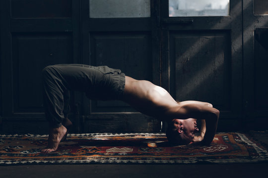 Side view of shirtless young man practicing yoga indoors