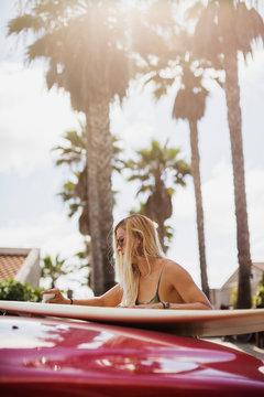 Girl Waxing a Surfboard