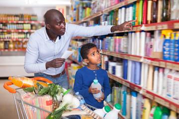 Glad man and boy reading shopping list