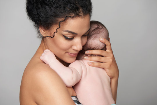 Pretty woman holding a baby in her arms