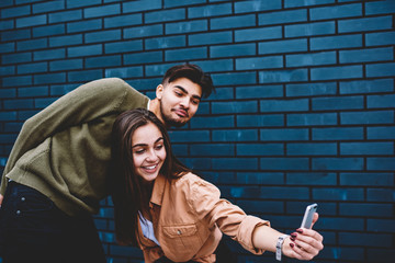 Couple in love having fun together making photo on smartphone camera near wall promotional background, best friends posing for selfie for blogging in social networks enjoying free time outdoors