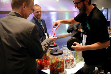 "Attendees receive free CBD gummy candy samples from ""The Hemp Plug"" (THP) brand at The Cannabis World Congress & Business Exposition (CWCBExpo) trade show in New York"