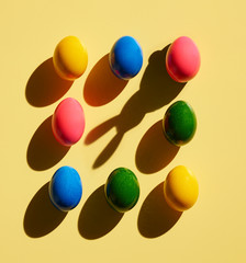 Dyed Easter eggs on yellow background and shadow of bunny ears