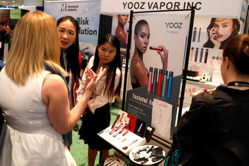 Attendees gather at a Yooz Vapor Inc. display at The Cannabis World Congress & Business Exposition (CWCBExpo) trade show in New York