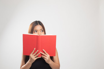 Young Asian woman with a book cover her face.