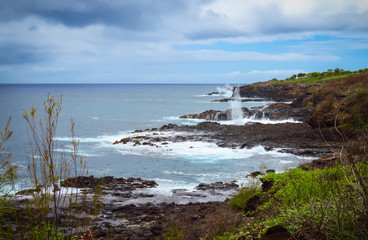Rocky shoreline and Spouting Horn blowhole on the South Shore of Kauai near Poipu, Hawaii, USA