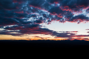 Purple and pink outlines beautiful clouds at sunset over a mountain range silhouetted against the sky - Jemez Mountains near Santa Fe, New Mexico