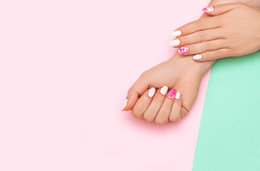 Wall Mural - Perfect manicure with trendy nail art on pink and turqoise background
