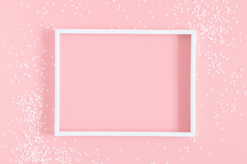 Festive light pink elegant background. Blank photo frame and stars on pastel pink background. Christmas, New Year, birthday concept. Flat lay, top view, copy space