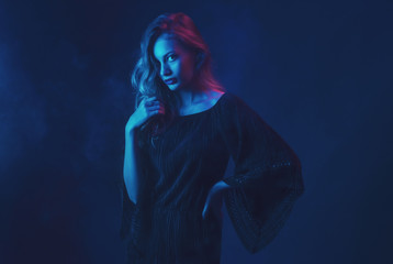 Beautiful ,young blonde with bright scarlet lips and expressive eyes in a black jumpsuit in neon light blue and red lamps.